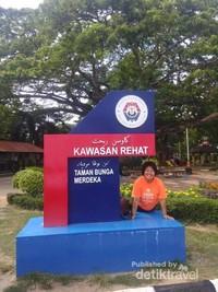 Berfoto di papan nama Taman Bunga Merdeka.