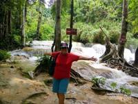 Berfoto di samping air terjun berundak Kuang Si, Luang Prabang,