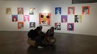 Pengunjung museum sedang bersantai sambil menikmati lukisan-lukisan yang ada