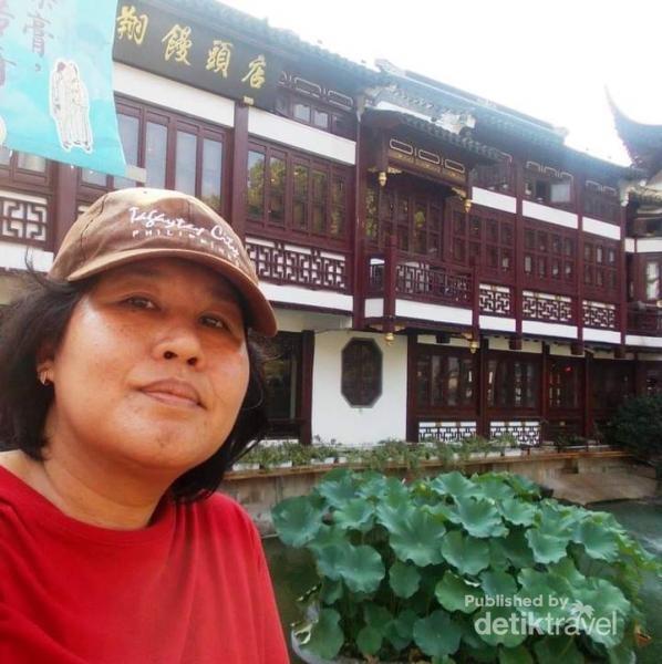 Berfoto dengan latar belakang bangungan di Yu Yuan.
