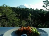 Pucuk Gunung Arjuno di balik pepohonan.