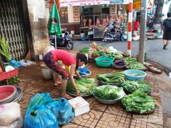 Seorang ibu pedagang sayur di trotoar jalanan kota Can Tho.