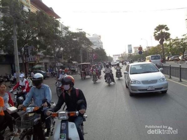 Beberapa jalanan berbaur antara sepeda motor, mobil dan tuk tuk.