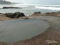 Cekungan batu karang membentuk kolam kecil yang sering dijadikan tempat berendam.