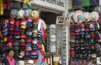 Pedagang topi dengan warna-warni yang menawan di Pasar Candi Kuning.
