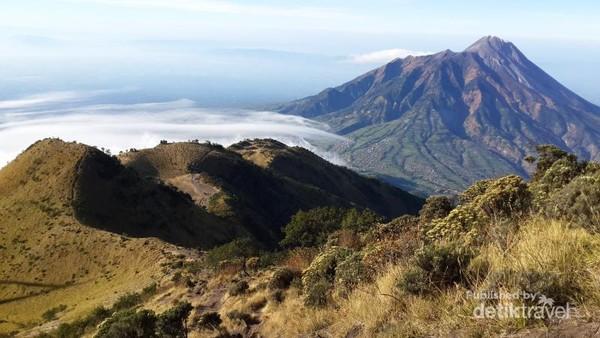 Pemandangan indah perpaduan savana yang luas, gugusan gunung dan gulungan awan.