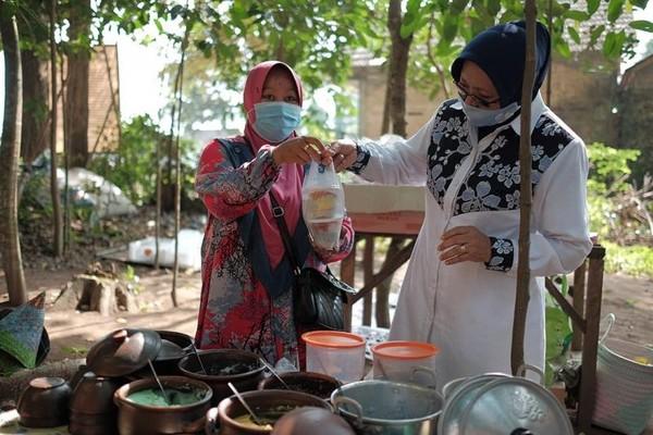 Sri Muslimatun mencicipi bubur tujuh rupa, makanan khas di Taman Raja Balitung