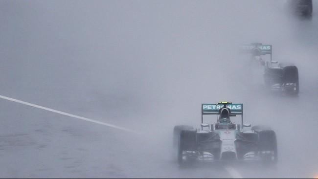 Hujan deras yang menyelimuti Sirkuit Suzuka, Minggu (5/10), membuat balapan GP Jepang harus dimulai di belakang mobil pengaman. Pebalap Mercedes, Nico Rosberg, memulai balapan ini dari pole position. (REUTERS/Toru Hanai)