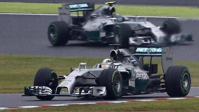 Pebalap Mercedes, Nico Rosberg, berada di depan rekan setimnya, Lewis Hamilton, pada awal balapan GP Jepang di Sirkuit Suzuka, Minggu (5/10). Hujan deras membuat jarak pandang di Sirkuit Suzuka sedikit terbatas. (REUTERS/Toru Hanai)