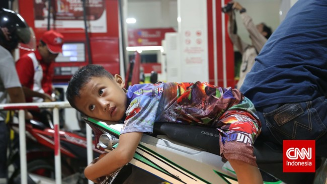 Demi memperoleh bahan bakar minyak sebelum harga baru diberlakukan, seorang bocah ikut mengantre membeli BBMbersubsidi disebuah stasiun pengisian bahan bakar umum (SPBU) di Jakarta, Senin, 17 November 2014.(CNN Indonesia/Safir Makki)