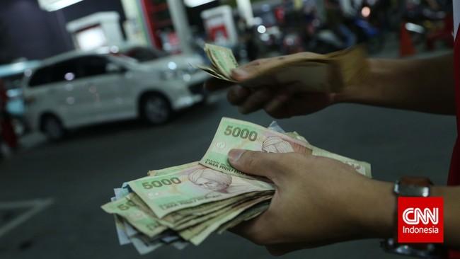 Berdalih menekan subsidi, pemerintah mengumumkan kenaikan bahan bakar minyak (BBM) sebesar Rp2.000 untuk jenis premium dan solar. Terlihat petugas menghitung uang saat melayani warga yang mengisi BBMdi Pom Bensin Jakarta, Senin, 17 November 2014. (CNN Indonesia/Safir Makki)