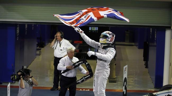 Seusai balapan, Lewis Hamilton langsung mengeluarkan bendera Inggris yang sudah ia persiapkan sebelumnya. Saat ini Hamilton sendiri tercatat sebagai pembalap paling sukses di Inggris sepanjang massa. (Reuters/Hamad I Mohammed)