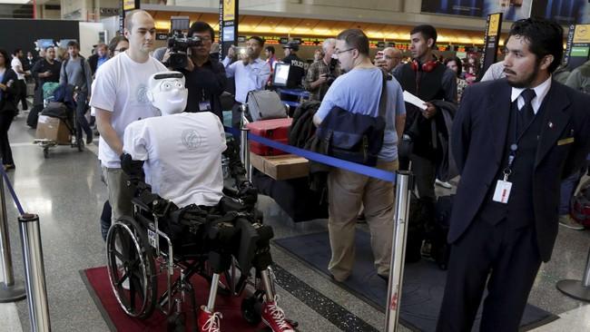 Alexander Herzog, mahasiswa doktoral di Max Planck Society mendorong robot manusia Athena memasuki Bandara Internasional Los Angeles, Senin (15/12) waktu setempat. Robot itu dibeli dari perusahaan bernama Sarcos, yang berasal dari Salt Lake City.