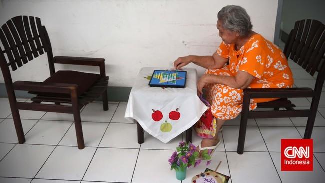 Seorang ibu lansia bermain ludo sendiri, di salah satu Panti Wreda, Jakarta. Tak ada kegiatan khusus yang dilaksanakan bagi ibu-ibu lansia ketika memperingati hari Ibu Nasional pada 22 Desember ini. (CNN Indonesia/Adhi Wicaksono)