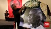 Seorang kerabat memasang kain ulos di foto almarhum Sitor Situmorang sebelum kedatangan jenazahnya. (CNN Indonesia/Safir Makki)