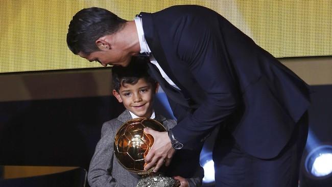 Cristiano Ronaldo meraih trofi Ballon d'Or 2014 pada 12 Januari 2015. Ia pun mencium putranya usai menerima trofi itu di Zurich, Swiss. Kini, tampaknya trofi Ballon d'Or 2015 akan menjadi milik Lionel Messi yang gemilang bersama Barcelona. (REUTERS/Arnd Wiegmann)