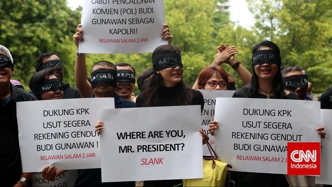 Sejumlah relawan Salam Dua Jari membawa poster dan penutup mata melakukan aksi damai di Kantor Komisi Pemberantasan Korupsi (KPK), Jakarta, Kamis (15/1).Para relawan melakukan aksi di kantor KPK mendukung pengusutan kasus rekening gendut yang disangkakan kepada Komisaris Jenderal Budi Gunawan. (CNN Indonesia/Safir Makki)