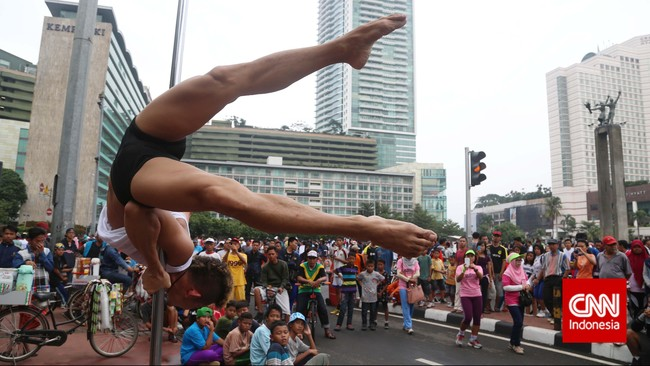 Para warga (juga wisatawan) yang melintas berlomba mengabadikan dengan ponsel aksi penari pole dance dari Indonesia Pole Dance Assocaiation (IPDA) di sela kegiatan Car Free Day di Bundaran HI, Jakarta, (18/1). Aksi yang mengandalkan kekuatan otot ini tak ubahnya sirkus.