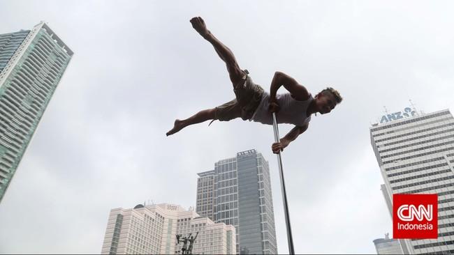 Seorang penari pole dance dari Indonesia Pole Dance Assocaiation (IPDA) memuncaki tiang saat beraksi di sela kegiatan Car Free Day di Bundaran HI, Jakarta (18/1). Seolah melayang tinggi, menyaingi gedung-gedung pencakar langit di kawasan Thamrin.