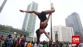 Penari pole dance dari Indonesia Pole Dance Assocaiation (IPDA) beratraksi saat Car Free Day di Bundaran HI, Jakarta, Minggu (18/1). Pole dancing merupakan bentuk seni pertunjukan yang menggabungkan tari dan akrobat yang menggunakan tiang.