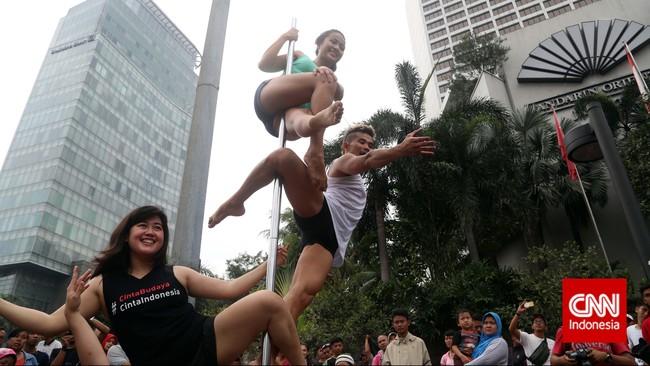 Pole dancing juga dapat dilakukan secara tandem dua orang atau lebih, seperti aksi yang dipertunjukkan para penari pole dance dari Indonesia Pole Dance Assocaiation (IPDA) di sela kegiatan Car Free Day di Bundaran HI, Jakarta, (18/1)