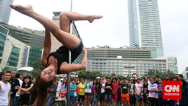 Para penonton menyesaki Bunderan HI saat penari pole dance dari Indonesia Pole Dance Assocaiation (IPDA) beratraksi di sela kegiatan Car Free Day di kawasan Thamarin, Jakarta (18/1). Sejenak mereka menghentikan kegiatan berjalan kaki atau bersepeda demi memirsa aksi akrobat yang seru ini.