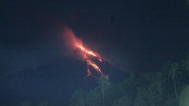 Gunung Karangetang mengalami erupsi dan mengeluarkan lava pijar di Kabupaten Sitaro, Sulut, Selasa (20/1) malam. Walaupun mengalami erupsi, Gunung Karangetang masih berada dalam status siaga dan belum naik ke level awas. (ANTARA FOTO/Ronny Adolof Buol)