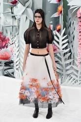 Kendal Jenner menjadi salah satu model dalam peragaan busana Chanel di Grand Palais. Ia menggunakan baju crop top hitam yang menerawang. Sedangkan rok A-line-nya terlihat cantik dengan tambahan detail bunga. (Pascal Le Segretain/Getty Images).