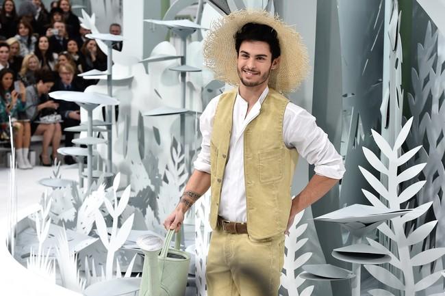 Koleksi Chanel di Haute Couture Fashion Week 2015 di Paris menampilkan kreasi busana yang unik. Salah satu model prianya menggunakan busana bak seorang petani, lengkap dengan celana pendek, topi jerami dan penyiran tanaman (Pascal Le Segretain/Getty Images).