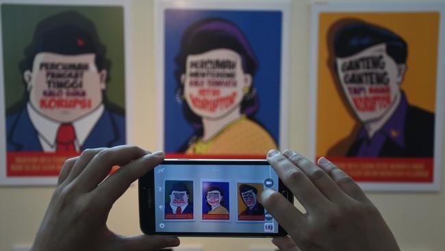 """Ganteng-ganteng tapi anak koruptor,"" demikian bunyi tulisan yang menyertai salah satu seni grafis yang dipamerkan di TIM. Para seniman yang kebanyakan anak muda ini banyak mengambil tema perseteruan KPK dengan Polri. (ANTARA FOTO/Hafidz Mubarak A./Rei/mes/15)"