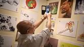Mantan pelaksana tugas (plt) pemimpin Komisi Pemberantasan Korupsi Mas Achmad Santosa memotret karya seni grafis bertema anti-korupsi yang dipamerkan di TIM. (CNNIndonesia Rights Free/Feri Latief)
