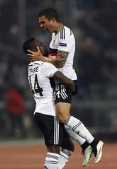 Ramon Motta dari Club Brugge merayakan keberhasilan mencetak gol ke gawang Besiktas dengan Daniel Opare (kiri). Besiktas pun kemudian gagal melaju ke perempat final. (Reuters/Murad Sezer)