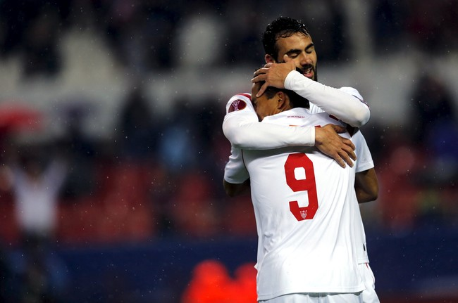 Vicente Iborra (belakang) dari Sevilla memeluk Carlos Bacca setelah ia berhasil membobol gawang Villareal. Sevilla sendiri sukses menyingkirkan tim senegaranya dari Liga Eropa.