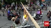 Petugas Pol PP bersama PLN menurunkan bambu yang digunakan untuk aliran listrik liar.