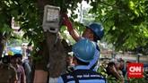 Petugas melakukan penertiban di pohon. Penertiban tersebut dilakukan guna menghindari potensi kebakaran akibat korsleting pada sambungan liar tersebut.