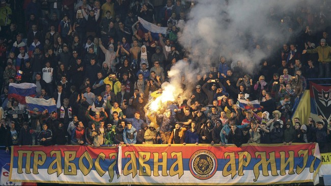 Di Podgorica, pendukung tuan rumah Rusia menyalakan suar ketika mendukung negaranya berhadapan dengan Montenegro. (Reuters/Stevo Vasiljevic)