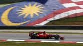 Sebastian Vettel melintasi bendera Malaysia. Setelah sesi kualifikasi pada sabtu (28/3), Vettel berhak start dari urutan kedua. Pole position diraih rivalnya dari tim Mercedes, juara dunia 2014, Lewis Hamilton.(Reuters/Olivia Harris Livepic)