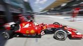 Sebastian Vettel mengeluarkan mobil balap Ferrari dari garasi menuju lintasan balap. Juara dunia tiga kali itu bergabung dengan Ferrari sejak musim ini setelah musim lalu tampil mengecewakan bersama Red Bull. (Reuters / Olivia Harris)