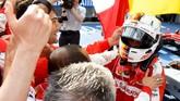 Sebastian Vettel berlari memeluk rekan-rekannya di tim Ferrari. Itu adalah kemenangan pertamanya bersama Ferrari dan juga kemenangan pertama tim asal Italia itu sejak Mei 2013. (Photo by Lars Baron/Getty Images)