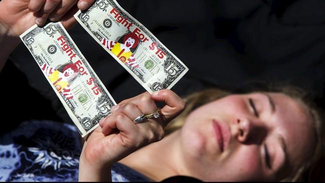 Unjuk rasa digelar sekitar pukul 6 pagi waktu setempat di depan sebuah gerai McDonald's di Brooklyn, dengan sebagiah besar demonstran membawa atribut lembaran uang dolar yang telah digambar sosok Ronald McDonald, maskot dari McDonald's.(Reuters/Lucas Jackson)
