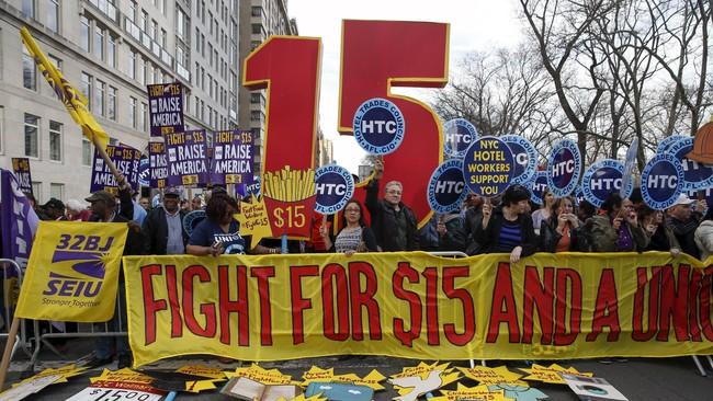 Demonstran juga berunjuk rasa juga terjadi di Manhattan, dengan membawa atribut angka 15 yang berarti kenaikan upah hingga US$15 per jam, bertepatan dengan pembatasan lapor pajak di AS yang jatuh pada tanggal 15 April 2015.(Reuters/Shannon Stapleton)