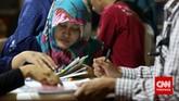 Seorang perempuanmengisi data diri saat berlangsungnya pameran bursa kerja di Balai Kartini, Jakarta, Jumat (24/4). (CNN Indonesia/Safir Makki)