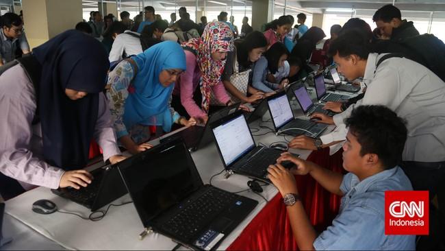 Para pencari kerja mengisi data di laptop yang disediakan penyelenggara saat pameran bursa kerja di Balai Kartini, Jakarta, Jumat (24/4). (CNN Indonesia/Safir Makki)