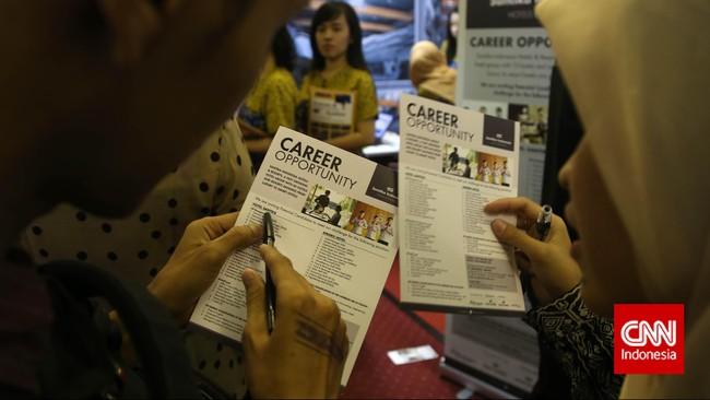 Pencari kerja melihat brosur posisi lowongan pekerjaan saat pameran bursa kerja di Balai Kartini, Jakarta, Jumat (24/4). (CNN Indonesia/Safir Makki)