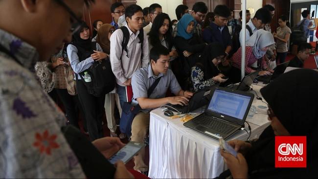 Para pencari kerja antre mengisi formulir lamaran kerja di stan sebuah perusahaan saat pameran bursa kerja di Balai Kartini, Jakarta, Jumat (24/4). (CNN Indonesia/Safir Makki)