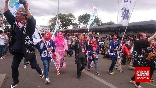 Peserta karnaval dari Jepang tak mau kalah memamerkan kostum mereka yang indah. Mereka menampilkan pakaian tradisional dengan dominasi warna hitam dan merah jambu. (CNN Indonesia/Nadi Tirta Pradesha).