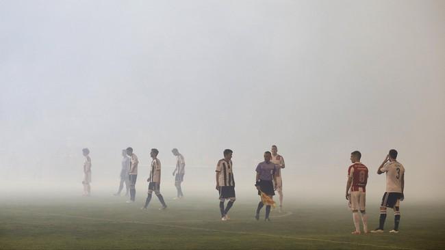 Asap suar pun memenuhi lapangan dan membuat pemain tak bisa melihat sehingga pertandingan sempat terhenti beberapa menit di pertengahan babak kedua.
