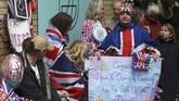 Para warga, loyalis keluarga Kerajaan Inggris, mengenakan kostum berornamen bendera Inggris atau Union Jack, seraya memamerkan poster berisikan ucapan selamat atas kelahiran putri pertama pasangan Pangeran William dan Kate Middleton, di St Mary's Hospital, London (2/5).