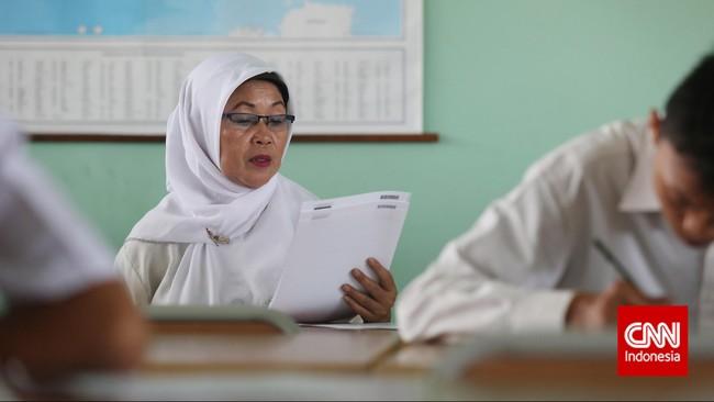 Seorang ibu menyimak lembar pertanyaanujian nasional kesetaraan paket B di SMA Negeri 80, Jakarta Utara, Senin, 4 Mei 2015. (CNN Indonesia/Safir Makki)