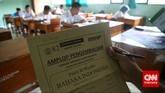 Pengawas ujian kesetaraan paket B di SMA Negeri 80, Jakarta Utara, menunjukkan amplop pengembalian lembar jawaban ujian Bahasa Indonesia. (CNN Indonesia/Safir Makki)